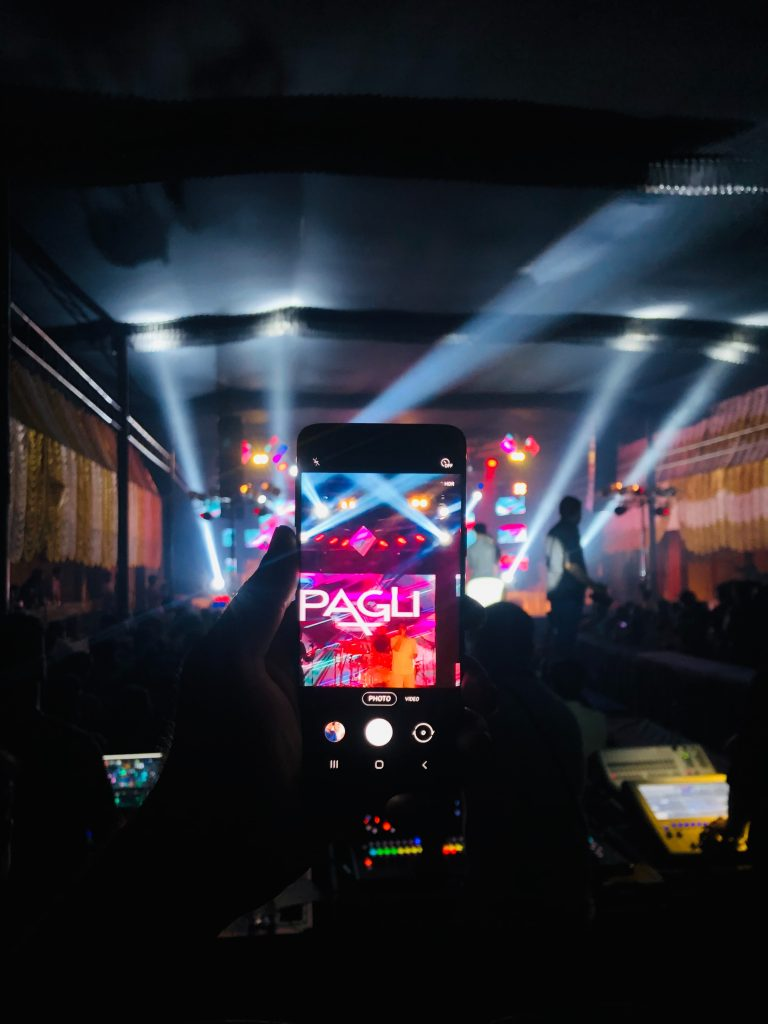 person holding black smartphone taking photo of people in front of stage during night time