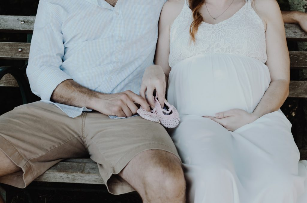 close-up photo of man and woman sitting on bench